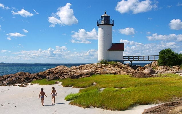 Children walk the beach below Annisquam Lighthouse