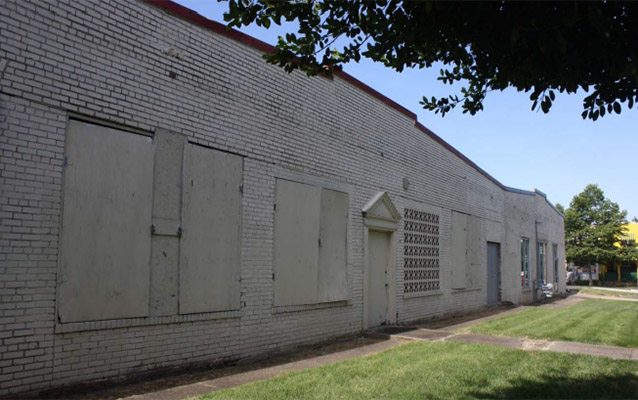 One story white brick commercial building with boarded up windows