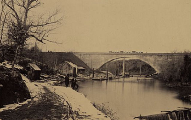 Union Bridge in the distance circa 1863. Two people in the foreground looking at camera.