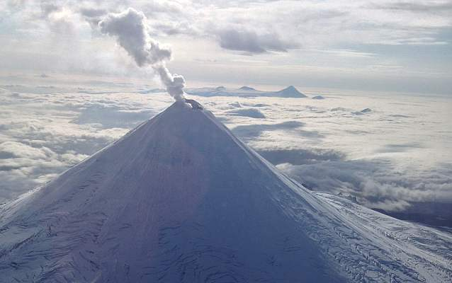 a snow covered volcano with smoke rising from the top