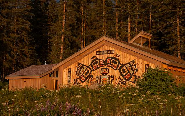 the Huna Tribal House building in evening sunset lighting, surrounded by trees