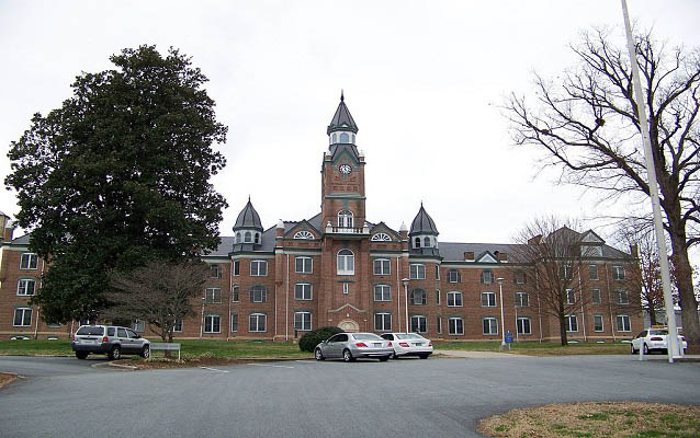 Exterior of a large, brick institutional building with clock tower.