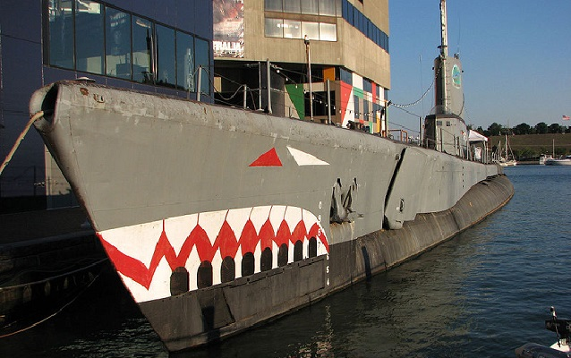 USS Torsk docked in water with painted shark face.