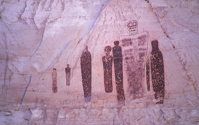 human-shaped figures painted on a rock wall