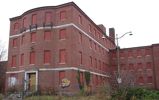 Exterior of a four story red brick building with boarded up windows.