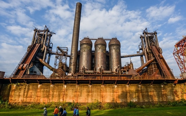 People walk on grass next to the Carrie Blast Furnaces.