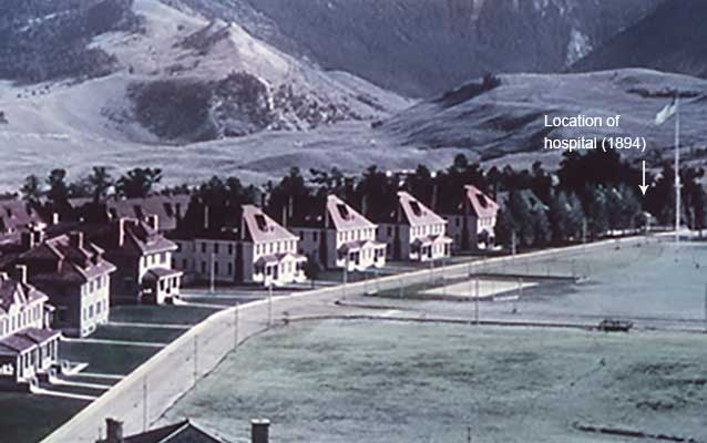 View across Fort Yellowstone, with hospital obscured by trees.
