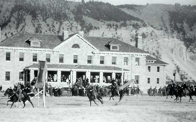 Soldiers performing horse drills on the parade grounds in front of the Bachelor Officers' Quarters.