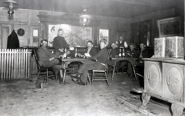 Black-and-white photograph of soldiers sitting around two tables inside the building.
