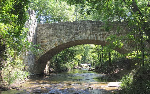 a stone bridge over a creek in the woods