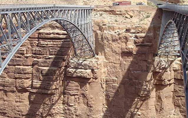 two steel arches span a desert canyon