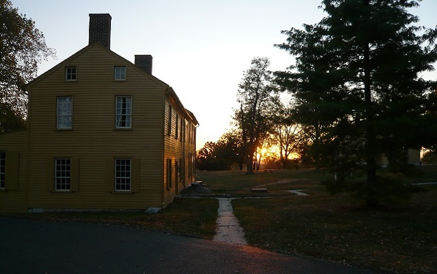 sunrise over a yellow shaker building
