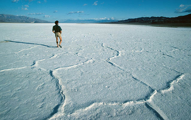 An expansive salt flat, devoid of obvious life, with distant desert mountains.