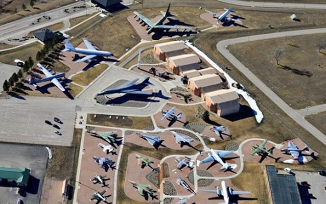A collection of airplanes is groups around a former hanger building
