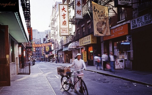 A street in Chinatown with man and bicycle with Chinese businesses and signs in background.