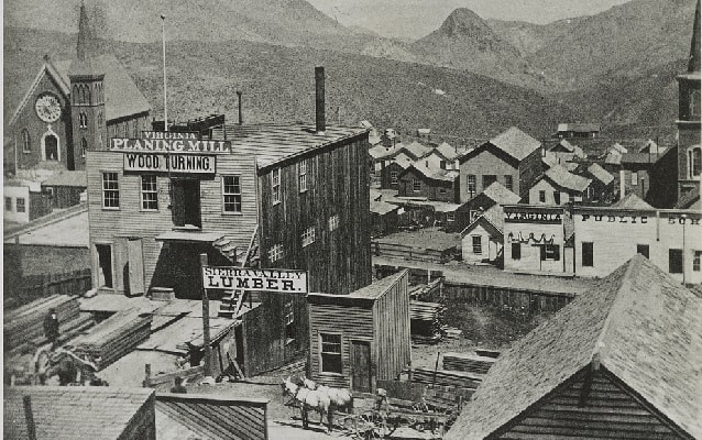 1866 photo showing birds eye view of old structures with mountains in background.