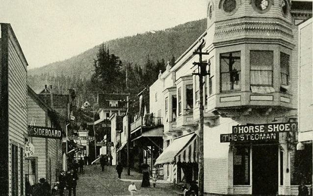 Black and white photo of a street lined with  shops with mountains in background.