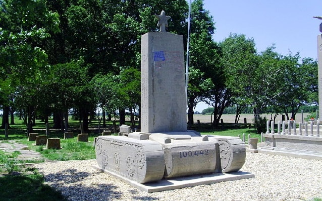 Contemporary photo of cement monument in the shape of a tank with headstone on top.