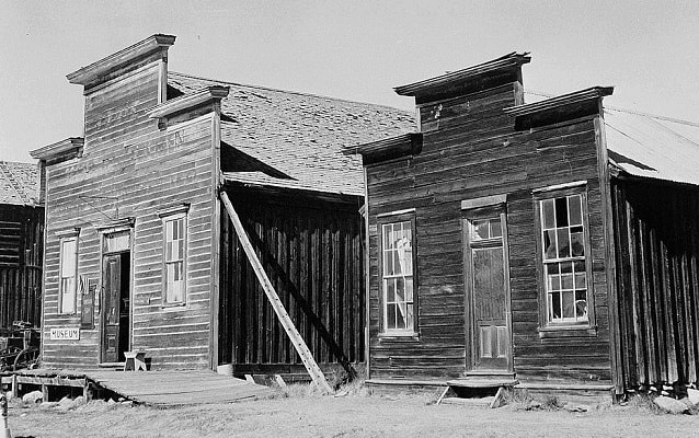 Black and white photo of two one-story buildings.