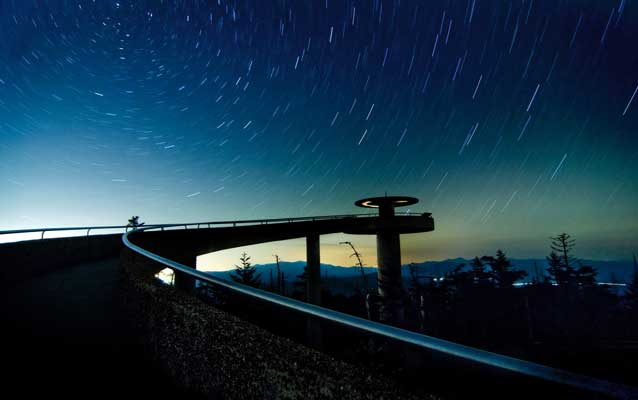 evening photo of ramp up to clingmans dome observation tower with stars above, mountains in distance