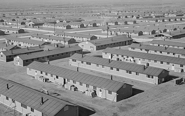 Black and white photo of rows of one-story style barracks.