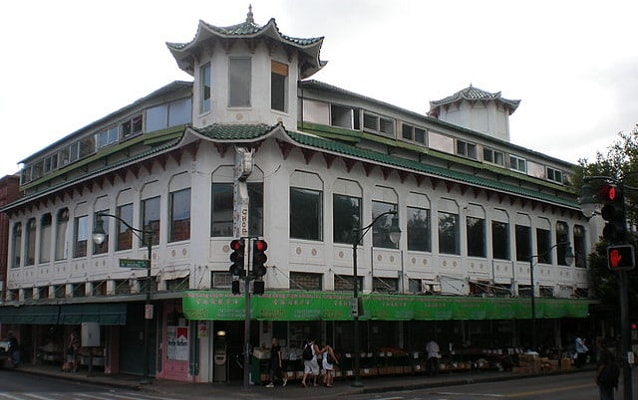 Wo Fat Building with large windows and green tiled roof.