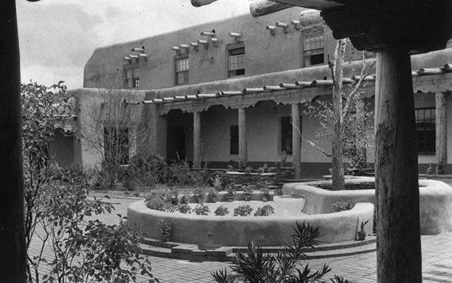 Historic photo of stucco building and courtyard