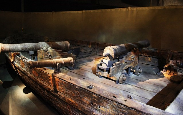 Wooden boat with two big cannons and one small one