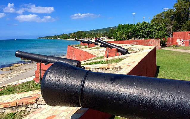 Cannons atop a red wall look over the blue ocean. Photo by N2theBlue CC BY-SA-4.0