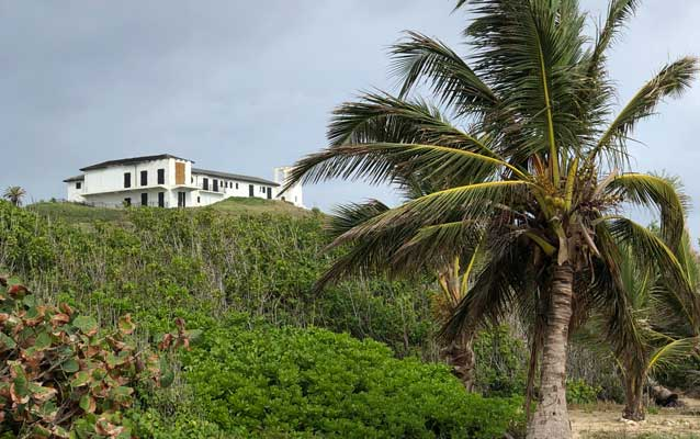 a white building up on cliff, beach and palm tree below