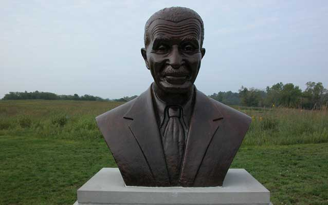 a bronze bust of George Washington Carver in front of green meadow