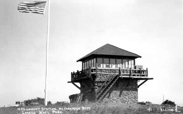 B&W; American flag flies above stone and wood fire tower