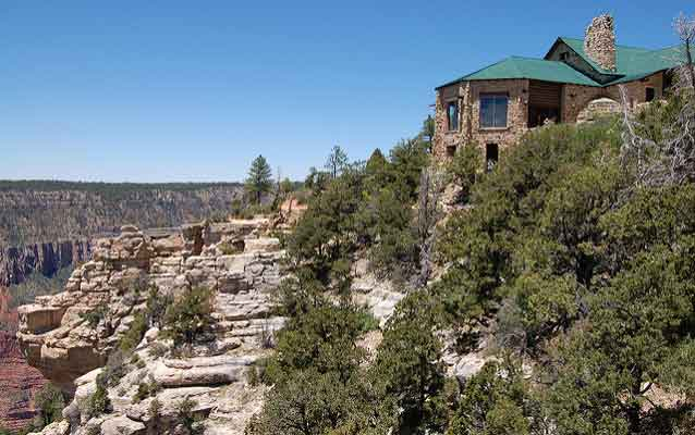 grand canyon on left with hotel perched upon its edge on the right surrounded by pine trees