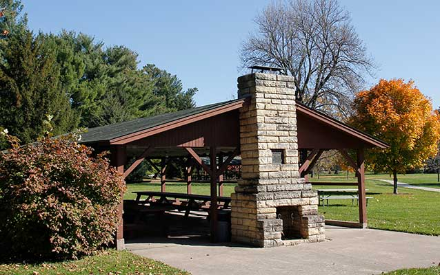 A timber picnic shelter has a limestone chimney and is painted reddish brown.