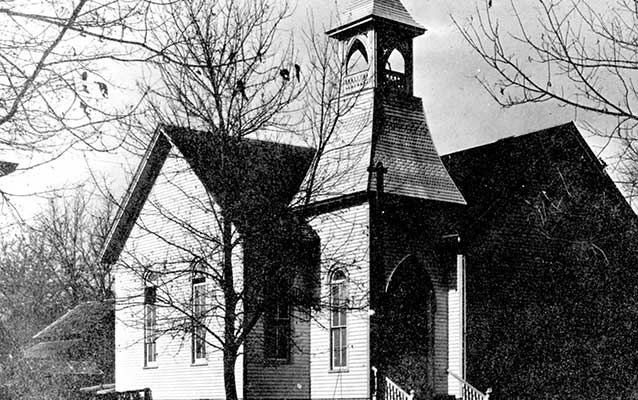 Black and white photograph of a white church with a steeple and gothic windows.