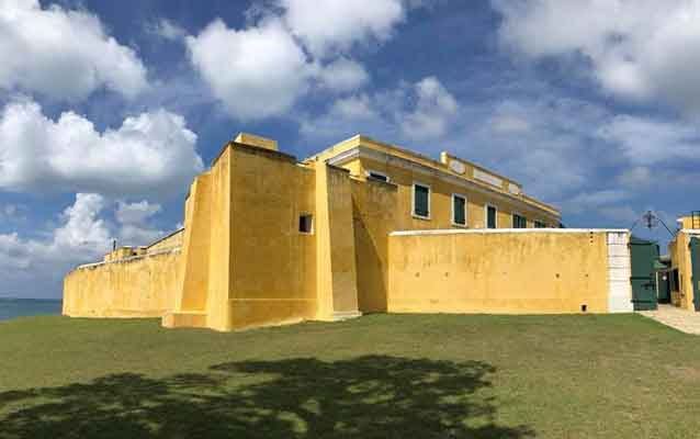 a yellow fort in front of a blue sky