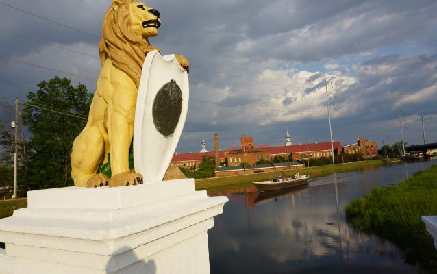 Boat on a canal-way with lion statue in the foreground and buildings in the background.