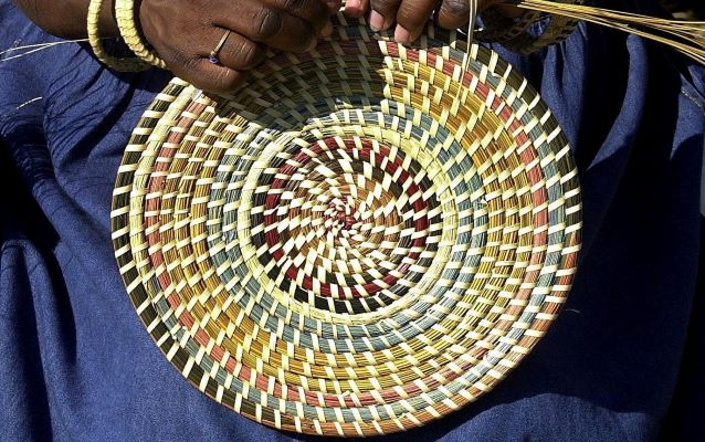 Person weaving a sweet grass basket.