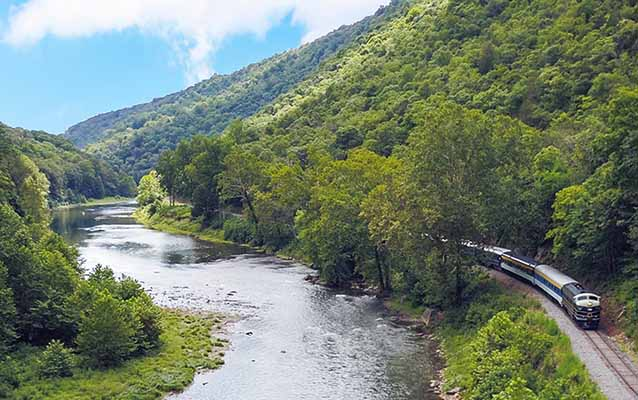 Potomac Eagle excursion train along the South Branch Potomac River in WV forest.