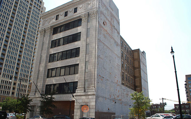 Seven story steel and concrete building with a flat roof.