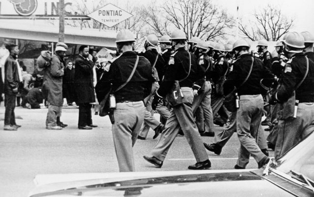 black and white photo of police approaching marchers