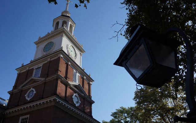 independence hall and a lamppost in front of a blue sky