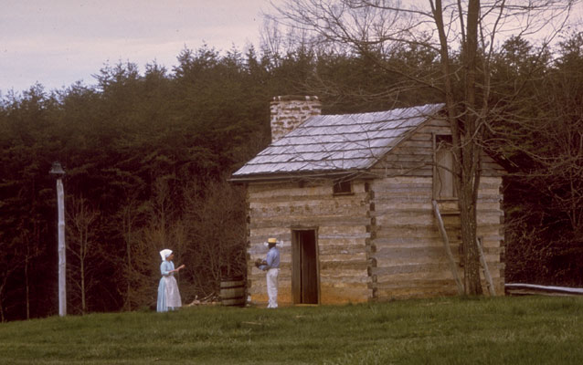 historical interpreters stand in front of a cabin