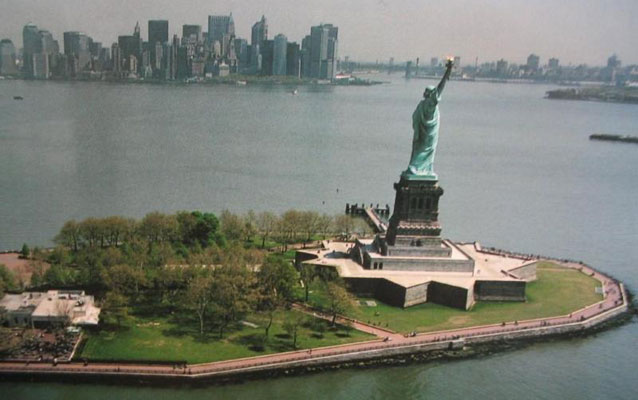 The Statue of Liberty stands on Liberty Island, with the skyline of New York in the distance.