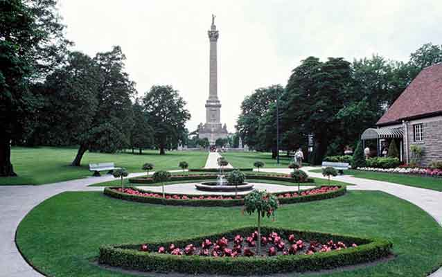 The yard at Queenston Heights. Circular yard with sidewalk and landscaping and a tall statue.