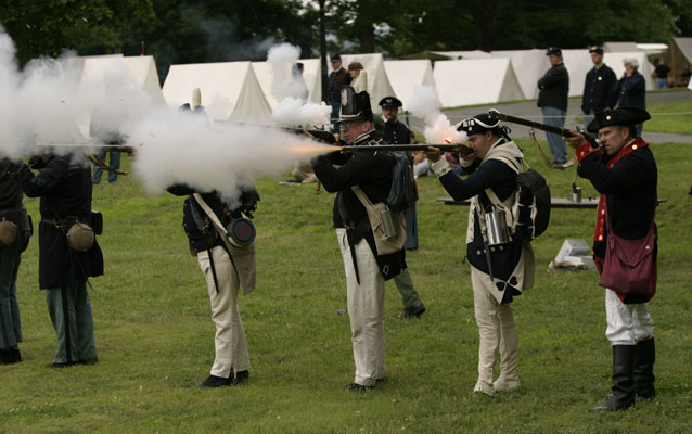 Five soldiers in historical attire fire muskets.