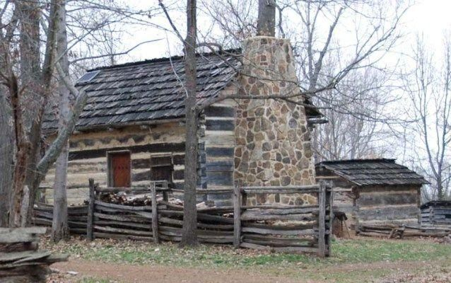 Photo of reconstructed log cabin and rail fencing.