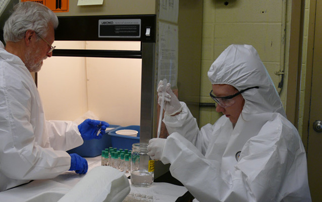 Two staff wearing protective clothing and glasses work in a laboratory.