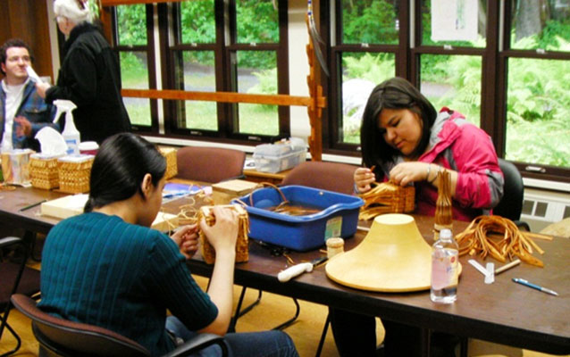 Students weave spruce root baskets in the park's regalia studio.