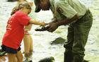 High School student hired as a park ranger helps a child find stream invertebrates in a park stream.